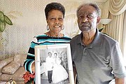 Dorothy and Levi Reeves stand in their Oakland, Calif., home, holding their wedding photo from 57 years ago. Dorothy Reeves agreed to donate both of their brains after death to the University of California-Davis for research. (Anna Gorman/KHN)