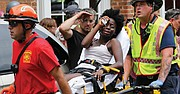 Rescue workers help a woman who was injured when a white nationalist rammed his car into a crowd of counterprotesters. Several of the 19 people injured are in critical condition.