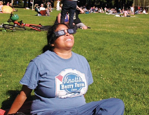 Annie Macer of Portland uses special glasses to safety view the Great Solar Eclipse from Peninsula Park.