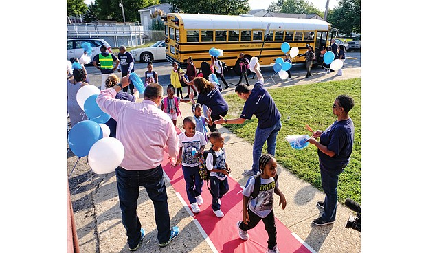 """Students are greeted Tuesday at George Mason Elementary School by a cheering squad of volunteers from Capital One. Principal Rose Ferguson and interim Superintendent Thomas E. """"Tommy"""" Kranz are the initial greeters by the school bus door."""