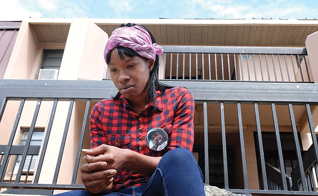 """Takeila Knight holds her own vigil Tuesday outside the Gilpin Court apartment of her stepbrother, Marvin Christopher """"Pee Wee"""" Eley, who was killed early Sunday. Her button is in memory of one of six other relatives who she said were killed in recent years"""