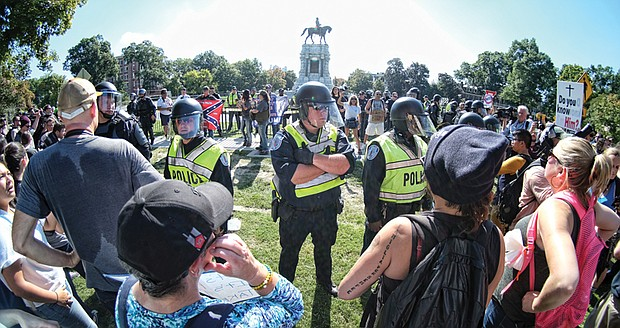 Richmond police officers in riot gear separate counterprotesters from neo-Confederates on the west side of the Robert E. Lee monument. The small number of Confederate statue supporters was vastly outnumbered by hundreds of counterprotesters.