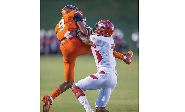 Virginia State University's Joshua Harris, left, hauls in the ball during last Saturday's game despite the defensive efforts of Winston-Salem State University safety Miguel Quinn.