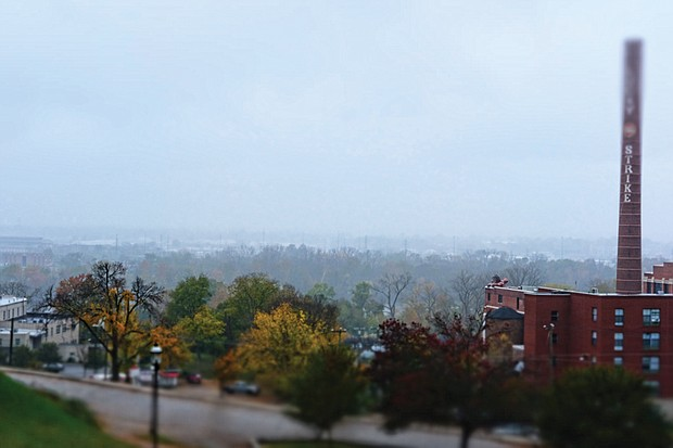 This rain-swept view from Libby Hill Park in the East End displays the bucolic side of Richmond. Instead of urban hustle and bustle, the scene shows a city engulfed in a soft fog that, with the hedge of colorful trees, obscures the view of the James River. Only an apartment building with an iconic smokestack provides a reminder of the crowded streets nearby.