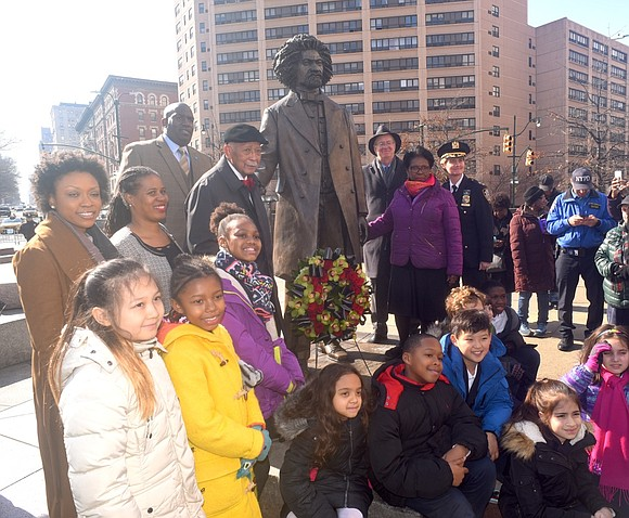 Many gathered at noon for a series of brief tributes and a laying of a wreath at the statue of ...