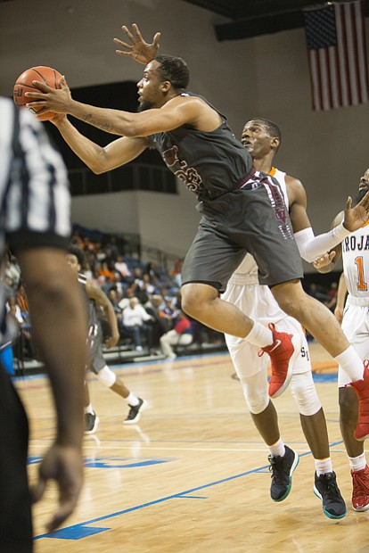 Virginia Union University senior Todd Hughes goes up for a shot against Virginia State University's defense during the NCAA opener at the VSU Multi-Purpose Center in Ettrick.