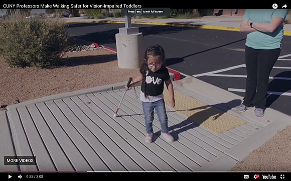 """The wearable """"toddler cane"""" fastens around the waist, positioning two attached white shafts joined with a U-shaped bumper on the ..."""
