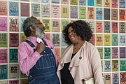 Artist Amos Paul Kennedy Jr. and Enjoli Moon, the ICA's adjunct assistant curator of film, talk in front of Mr. Kennedy's work in the opening exhibition.