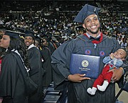Shaquille Robinson, right, shows off his new bachelor's degree and his young son, Shaquille Jr., during the afternoon commencement on Mother's Day.