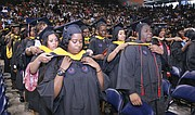 New graduates of Virginia State University help place each others' hoods signifying their new degrees during commencement ceremonies Sunday at the VSU Multi-Purpose Center. Shaquille Robinson