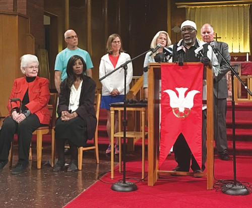 Imam Muhammad A. Najieb (at podium) joins other faith based leaders at Augustana Lutheran Church in northeast Portland Thursday  to give an update on a public safety campaign to ban the sale of assault weapons and large capacity magazines in Oregon.