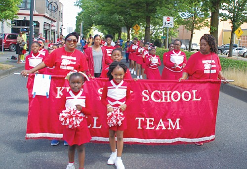 The younger King Sun School Drill team marches with a banner of school pride.