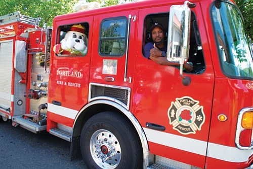 A Portland Fire and Rescue firefighter and his fluffy friend are thumbs up for Portland's freedom parade.