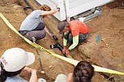 Volunteer AmeriCorps workers assist in the upgrade of a drainage pipe at the Alberta Commons Apartments as the nonprofit owners of the complex, Sabin Community Development Corp., gets help to keep the organization's home units affordable.