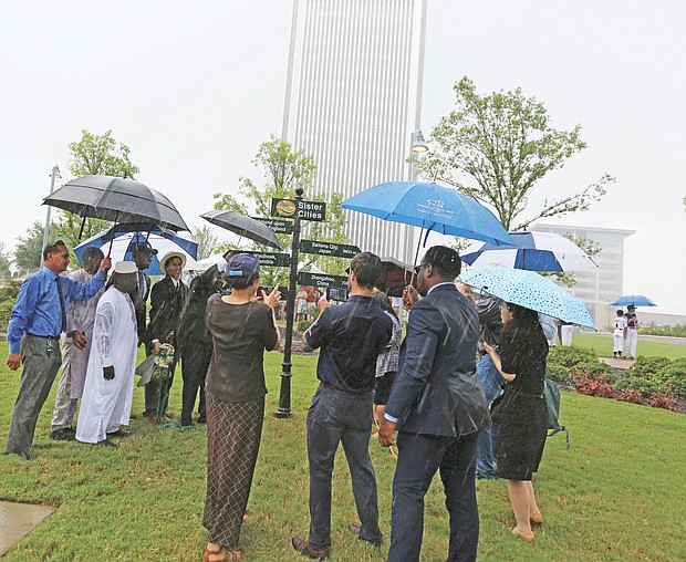 City officials and representatives of five overseas cities join Monday in unveiling Richmond's new International Guidepost at Kanawha Plaza amid a downpour. The new sign celebrates Richmond's Sister City relationship with Richmond upon Thames, England; Saitama City, Japan; Ségou, Republic of Mali; Windhoek, Namibia; and Zhengzhou, China. Saitama's representatives included members of the Japanese city's Little League baseball team. Richmond began a relationship with its English namesake in 1930 and began forging bonds with additional cities in 1980 after forming the 13-member Sister Cities Commission.