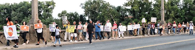 Members of the Southside Chapter of the New Virginia Majority call for Richmond Police transparency and accountability during a community march Monday night across the Mayo Bridge.