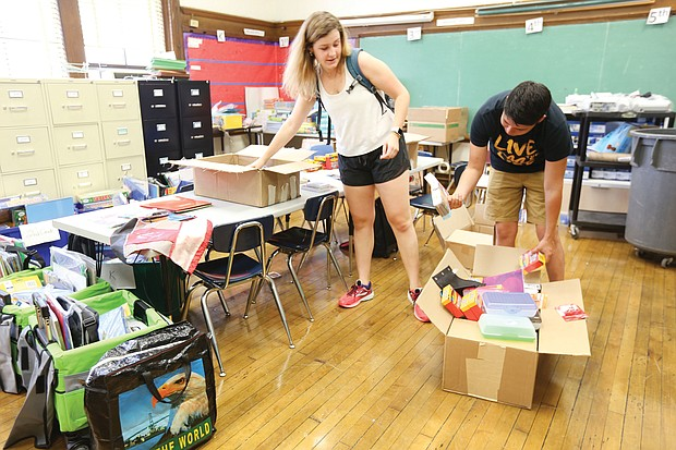 """At Carver Elementary School at least 60 volunteers are pitching in for """"RPS Shines Beautification Week,"""" including volunteers, Chris Rivera 20, of Springfield, Va., right, who is a junior at VCU and helping him organize school supplies is Sarah Lindamood, 20, of Richmond, who is a third year at UVA. She is also the task manager for Carver Shines."""