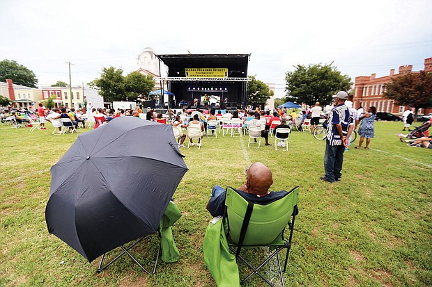 Adwela of Adwela & The Uprising, above left, gets the crowd going during last Saturday's 28th Annual Down Home Family Reunion. A little rain didn't dampen the spirits of the crowd that enjoyed music, food, arts and activities that focused on the historic ties between Richmonders and nations in Africa. Above, the crowd reacts to the sounds of Lady E & the Blues Synsations. The free event was sponsored by the Elegba Folklore Society.