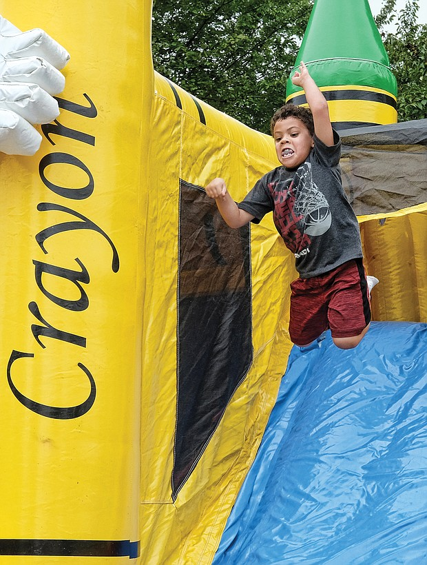 Isaac Williams, 5, goes into high-flying motion on the Big Bomb Bounce last Saturday at the Church Hill Reunion at Ethel Bailey Furman Park on North 28th Street. This was the 35th year for the annual event celebrating fellowship and community uplift. (Sandra Sellars/Richmond Free Press)
