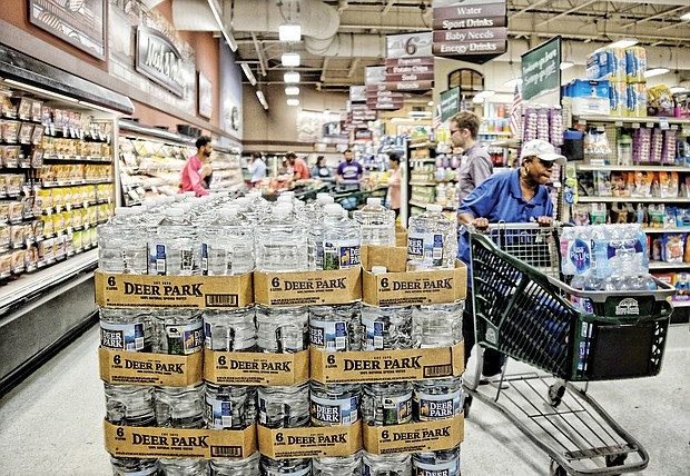 Shoppers at Farm Fresh supermarket on East Main Street in Richmond's Shockoe Bottom fill up on bottled water and supplies Tuesday as Hurricane Florence threatens Virginia and at least three other states.