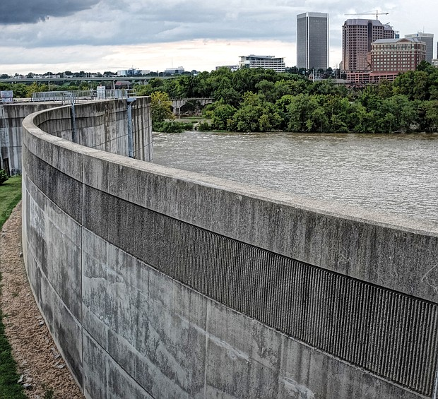 Richmond's 24-year-old floodwall seeks to guard low-lying areas of the city when the James River is at flood stage. This is a view of the 2,000-foot wall on South Side looking north toward Downtown. But as Richmond has learned, the floodwall can create flooding behind it when heavy rainfall dousing the city is unable to escape into the river, which happened during Tropical Storm Gaston in 2004. To reduce that problem, the city in June tested the floodwall gates to ensure that they can be opened to let water out. (Sandra Sellars/Richmond Free Press)