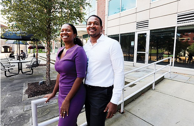 Husband and wife team Arvat McClaine and Harry Watkins stand outside the Vistas on the James condominium complex in Shockoe Bottom, where they are opening Bateau, A Coffee and Wine Experience.