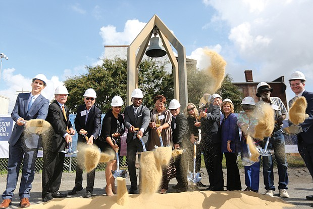 Mayor Levar M. Stoney, center, is flanked by City Council members Kim Gray, center left, and Ellen Robertson as he leads the official groundbreaking Tuesday for a $34 million apartment complex going up on the former site of St. Joseph's Catholic Church at 1st and Jackson Streets in Jackson Ward. The bell in the background is the last remnant of the long demolished church that at one time was the first Catholic church in the country built for a black congregation. When completed, the complex is to include 154 units, with 72 to be set aside for current residents of Fay Towers, which is being vacated. Also taking part are representatives of the development partners the Richmond Redevelopment and Housing Authority and the Community Preservation and Development Corp., as well as those of other participating public agencies and private companies.