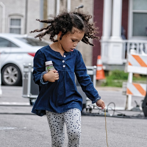 Walking the dog: Pets come in all types and sizes, including follow-behind toys. Zoe White, 4, looks to make sure her toy dog is following her at the STAY RVA Fest last Saturday on Bainbridge Street in South Side. The youngster is a pre-kindergarten student at Maymont Elementary School. (Sandra Sellars/Richmond Free Press)