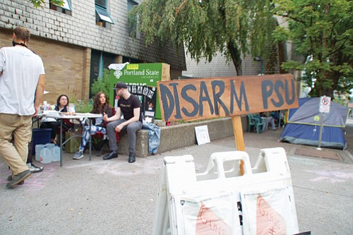 """Student Union members at Portland State University on Monday were overseeing an encampment outside the PSU Public Safety Office as an """"Occupy PSU"""" protest calling for disarming campus police enters its second week. The students also distributed literature and answered questions about their cause."""