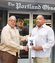 """Marcus Branch of Portland (right) presents Portland Observer Publisher Mark Washington with a personalized copy of Detroit journalist Al Allen's book """"We're Standing By."""" Branch met with Allen, a longtime TV anchor and reporter, at the National Association of Black Journalists Convention in Detroit where the book was signed, last month."""