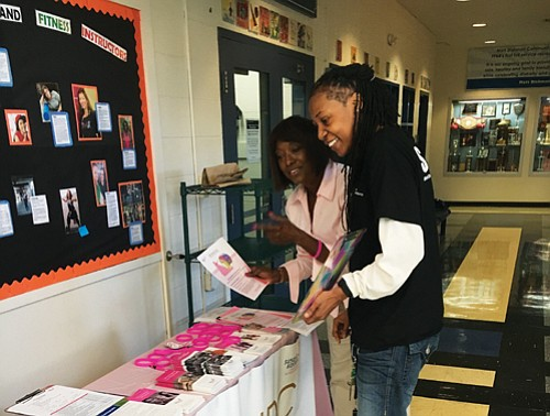 Diversity consultant D. Bora Harris of Portland (left) distributes information and answers questions about a public health campaign by Susan G. Komen Oregon and SW Washington to address breast cancer disparities in the African American community.