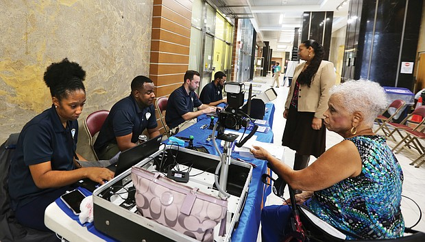 Tonya Ross, left, of the state Department of Motor Vehicles helps Jeraldine Williams take care of business on the first floor of City Hall last Friday as City Treasurer Nichole R. Armstead looks on. Ms. Ross is a member of the traveling team that operates the agency's DMV Connect mobile unit that brings services to people rather than requiring them to go to a DMV customer service center. The mobile unit is scheduled to return to City Hall at 9th and Broad streets in Downtown from 9 a.m. to 4 p.m. the first Friday of each month. Other DMV Connect staff are, from left, Brandon Gunnell, Thomas Luck and Irvin Mitchell.