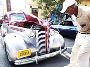 Robert Ford Sr. of Henrico County takes a closer look at a 1938 Buick 350 TP owned by Charles Muse of Richmond. The vintage auto was on display with others shown at the 2nd Street Festival by the Richmond Metropolitan Antique Car Club. (Regina H. Boone/Richmond Free Press)