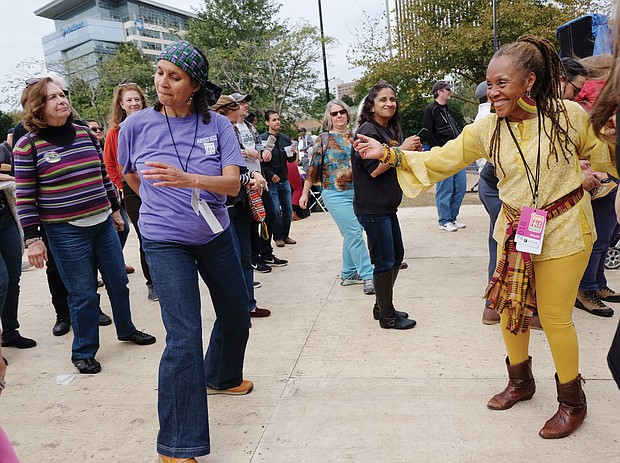 Janine Bell and Jarene Fleming stop and dance to the salsa sounds of Orquesta el Macabeo of Puerto Rico on Sunday at the Richmond Folk Fest. (Sandra Sellars/Richmond Free Press)