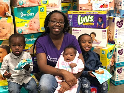 Sierra Mason with her baby Saniya, along with Za'Mari and Za'Vion Nipper. They were among those in attendance at a pamper drive distribution event held at the University of Maryland Baltimore County