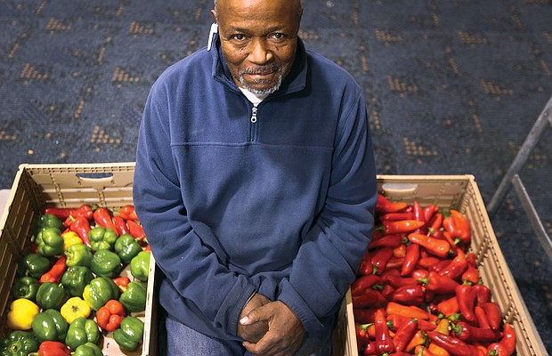 Charles E. Fitzgerald shows off a bounty of fresh peppers that he and other Atlee Church volunteers had ready for distribution at the Moss Side Avenue church last Saturday.
