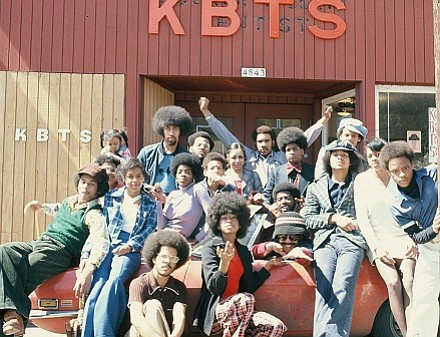 Volunteers pose in front of KBTS community radio station on N Knott street. The soul radio station was also a venue for community events and talk shows. 1970s.