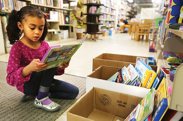 Leonora Wiziarde, 6, of Richmond is a voracious reader and what better place to read than the children's section of the Friends of the Richmond Public Library Book Sale Saturday, Nov. 3, 2018, held at the Main Library at 101 E. Franklin St. (Regina H. Boone/Richmond Free Press)
