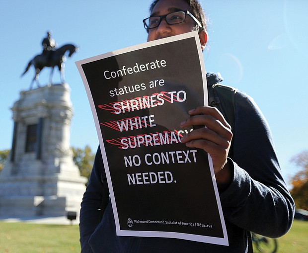 Point, counterpoint: The rally was the fifth held in the city since 2017 by the Confederate groups to show support for keeping the Confederate monuments. Counterprotesters, including this young man who did not want to be identified, held signs expressing their opposing position. Dozens of law enforcement officers were on hand to monitor events. (Regina H. Boone/Richmond Free Press)