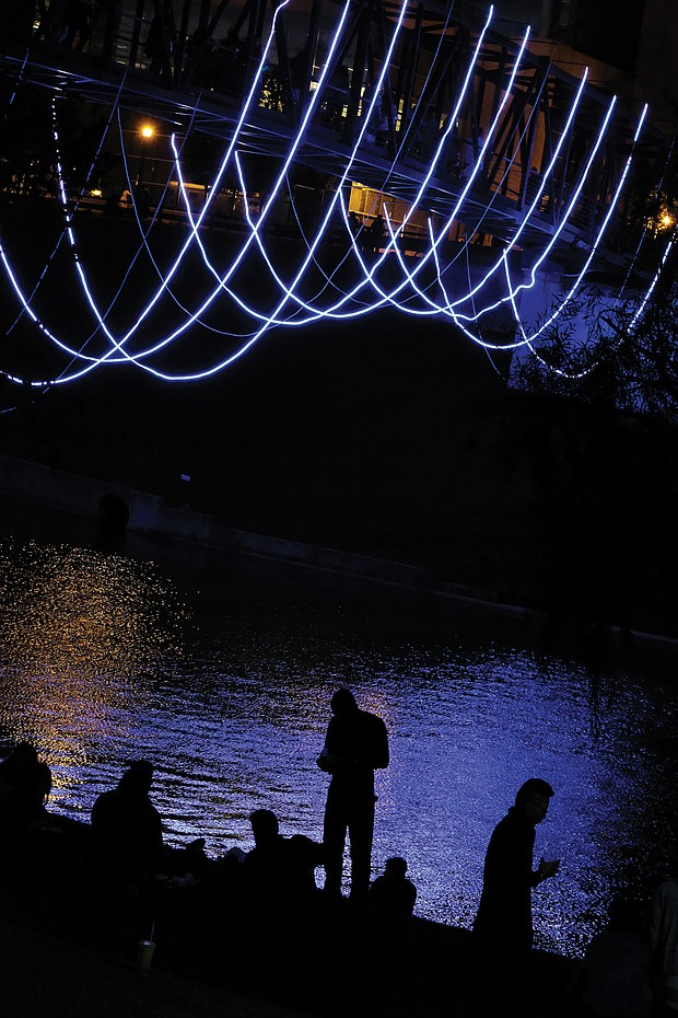 Ropes of lights add an artistic touch to this pedestrian bridge on the city's riverfront. The lines that seem to hang in the air are attached to the bottom of the pedestrian bridge that crosses the Kanawha Canal and links Tredegar Street at 7th Street to Brown's Island.  (Sandra Sellars/Richmond Free Press)