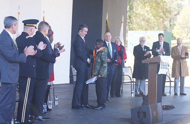 """Armistice Day: Gov. Ralph S. Northam congratulates Martene Whiting Jr., 13, a seventh-grader at Tabb Middle School in Yorktown, after he read his winning essay on """"What was the impact of World War I in Virginia?"""" during last Sunday's Veterans Day ceremony at Dogwood Dell. The essay contest and ceremony was part of the state's commemoration of the 100th anniversary of the end of World War I, known as Armistice Day. (Regina H. Boone/Richmond Free Press)"""