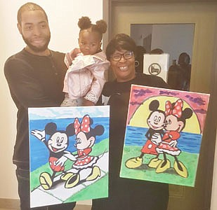 Artist Will Brown holding two-year-old  Ta'liya Fleming, who has lost three godbrothers to gun violence. She loves Mickey and Minnie Mouse. Millie Brown holds the paintings her son created for her.