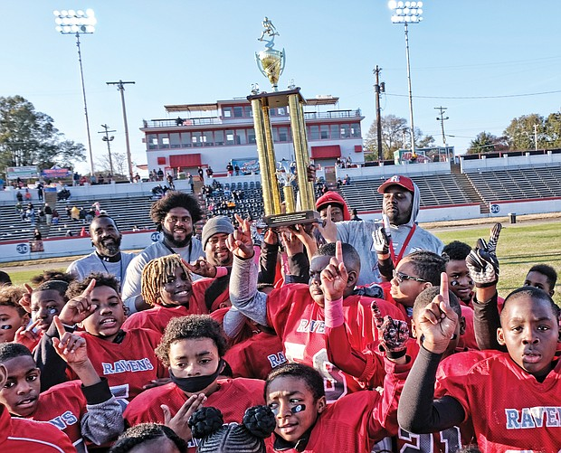 Players and coaches with the Richmond Parks and Recreation 2018 Champion Reid Ravens celebrate after defeating the Hotchkiss Eagles 18-0 in the 10U Peewee division last Saturday at City Stadium.