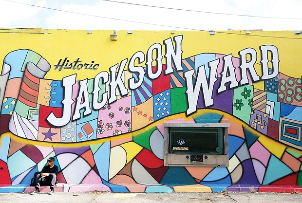 Akim Khan takes a lunch break in front of a colorful mural welcoming visitors to Jackson Ward. The mural is among several in the city spearheaded by U.N.I.T.Y. Street Project, which also has completed tributes to Dr. Martin Luther King Jr. and Arthur Ashe Jr.. This one involved artists Sir James Thornhill, Hamilton Glass and Keith Ramsey. Location: 1st and Marshall streets. (Regina H. Boone/Richmond Free Press)