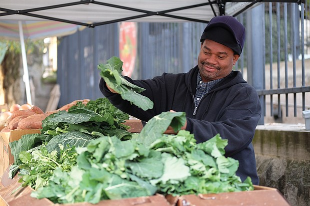 Timothy Christian, a fifth-generation vendor at the 17th Street Farmers' Market, shows off fresh collard greens. Forced to leave the market during construction, he now sets up his stand outside nearby Main Street Station in Shockoe Bottom.