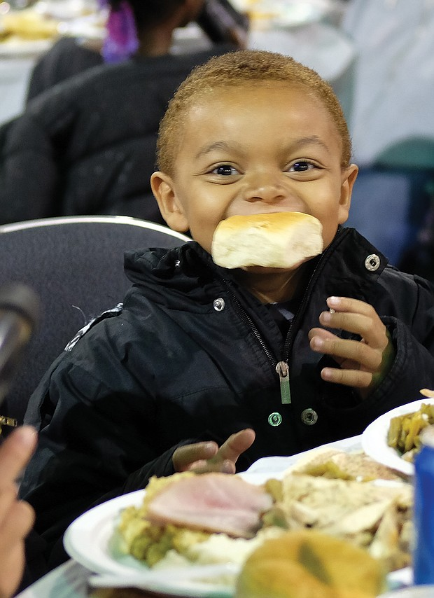 Delicious! Jabriel Birchett, 5, takes a bite of his roll on Thanksgiving Day and doesn't want to let go. The youngster was enjoying good food with family at The Giving Heart Community Thanksgiving Feast at the Greater Richmond Convention Center in Downtown. (Sandra Sellars/Richmond Free Press)