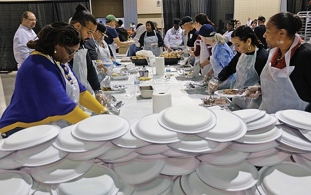 Giving thanks: Hundreds of people enjoyed a sumptuous dinner on Thanksgiving Day at The Giving Heart Community Thanksgiving Feast at the Greater Richmond Convention Center in Downtown. The annual event is free and draws hundreds of volunteers and contributors who provide fellowship and service to families and individuals sitting down for dinner. Behind the scenes, volunteers are hard at work preparing plates with turkey and all the fixings. (Sandra Sellars/Richmond Free Press)