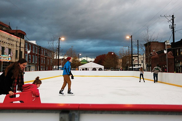 """Krista Waddell, left, and her 5-year-old daughter, Aribella, get ready to join Ian Donselaar, 18, center, on RVA On Ice's skating rink located at the 17th Street Farmers' Market near Main Street Station. Sponsored by Capital One, the rink quietly opened just before Thanksgiving at its new location. It's official opening will be Friday, Dec. 1. The rink will be open seven days a week before wrapping up the season on Monday, Jan. 21, Martin Luther King Day. """"Rock the Rink"""" parties are scheduled for 8 to 10 p.m. Saturday nights in December and January. On most days, the rink and skate rental tent open at 3 p.m.; however, skating begins at 11 a.m. on Saturdays and Sundays. Details: (804) 234-3905 or https://enrichmond.org/17th-street-market/rva-on-ice. (Regina H. Boone/Richmond Free Press )"""