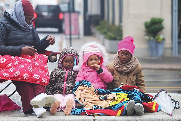 Waiting for Santa: Cheryl Brunson of Henrico and her three granddaughters are bundled up against the cold as they await the holiday floats and marching bands — and Santa — last Saturday at the 35th Annual Christmas Parade in Richmond. The youngsters, from left, are Maleah Atkinson and Lyric Dunlap, both 3, and Kha'mya Atkinson, 8. (Regina H. Boone/Richmond Free Press)