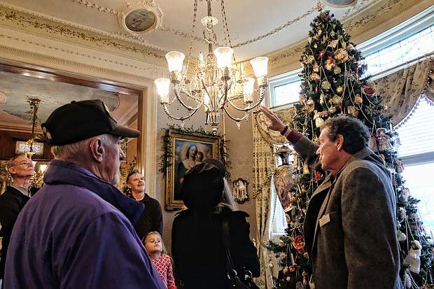 Old-fashioned Christmas: Visitors to Maymont embraced the holiday spirit last Sunday with the park's annual Old-fashioned Christmas celebration. A group gathers near the 12-foot Christmas tree and its Victorian decorations during a tour of the Dooley Mansion. The Gilded-Age mansion will be decked out for holiday tours through Jan. 6  (Sandra Sellars/Richmond Free Press)